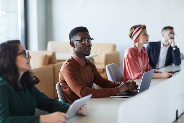 Gruppo multietnico di giovani imprenditori seduti al tavolo nella sala conferenze durante il seminario di formazione, concentrarsi sul giovane afro-americano che guarda l'obbiettivo, copia spazio