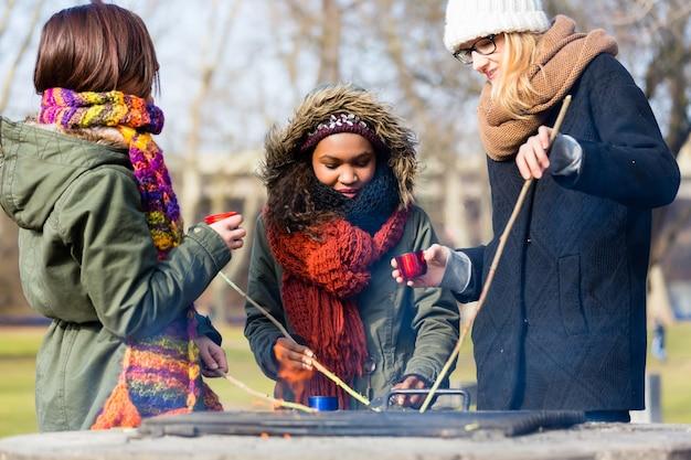Gruppo multietnico di giovani che tostano salsicce all'aperto in una fredda giornata d'autunno