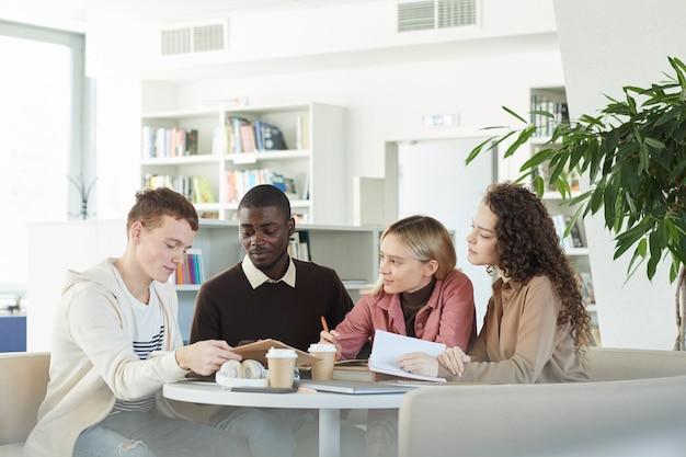 Gruppo multietnico di giovani che studiano insieme seduti a tavola nella biblioteca del college e lavorano al progetto di gruppo,
