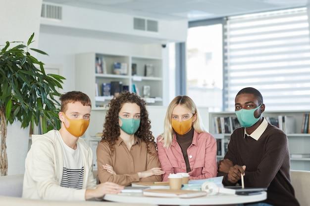 Gruppo multietnico di giovani che indossano maschere e mentre studiano insieme a tavola nella biblioteca del college,