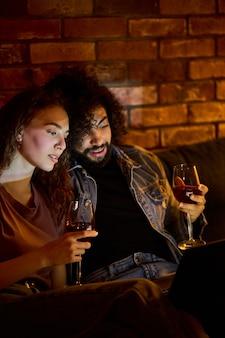 Coppia sposata multietnica che beve vino rosso mentre guarda film, film, commedie. la bella donna ama passare il tempo con il fidanzato a casa