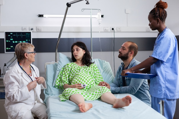 Squadra medica multietnica che consulta una donna con gravidanza