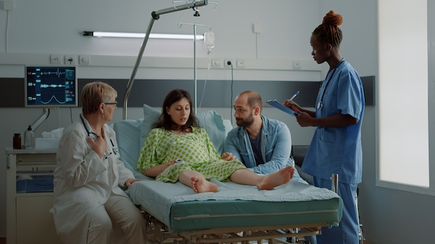 Equipe medica multietnica che parla con una donna incinta