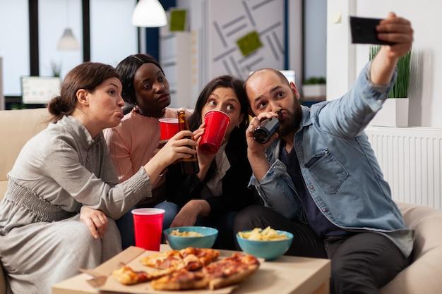 Un team multietnico di amici crea ricordi alla festa dopo il lavoro