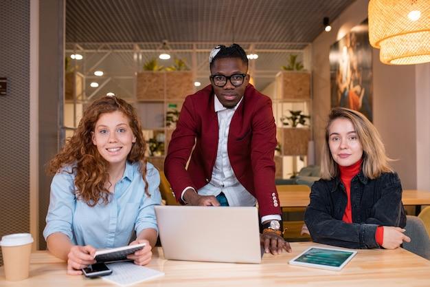 Squadra multietnica di tre giovani manager di ufficio di successo in abbigliamento casual seduti a tavola e con riunioni di lavoro