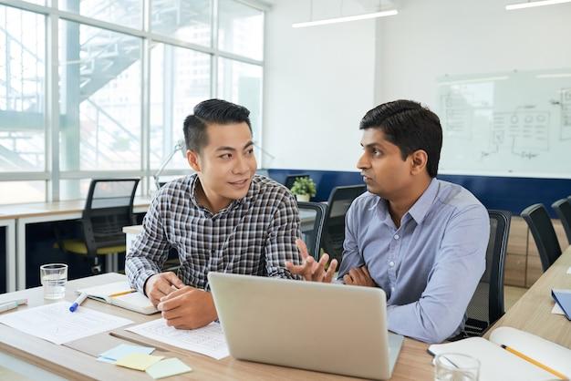 Team multietnico di designer ux che discutono dell'interfaccia della nuova applicazione monile su cui stanno lavorando
