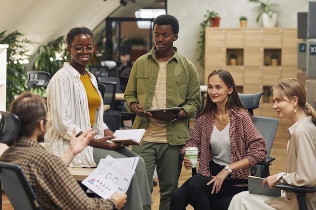 Team multietnico di giovani imprenditori che collaborano al progetto seduti in cerchio in un ufficio moderno e sorridono allegramente
