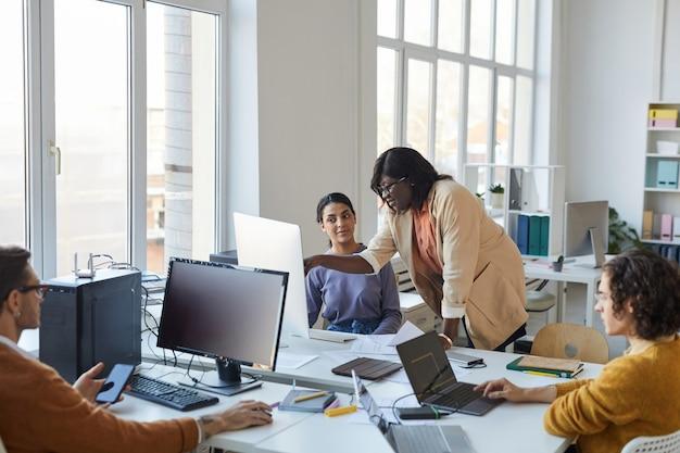 Team multietnico di giovani sviluppatori di software che utilizzano computer in un ufficio moderno, con particolare attenzione alla donna afroamericana che istruisce il collega, copia spazio