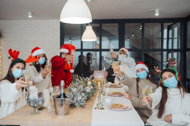 Giovani multietnici che celebrano i vetri tintinnanti di vigilia del nuovo anno che tostano, congratulandosi bevendo champagne