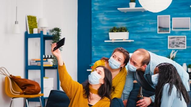 Amici multietnici con maschere protettive che festeggiano con la birra prendendo selfie durante l'epidemia di covid 19, nuovo concetto di stile di vita normale con persone che si divertono in soggiorno rispettando la distanza sociale