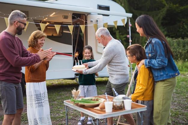 Una famiglia multigenerazionale che festeggia il compleanno all'aperto in campeggio, in vacanza in roulotte.