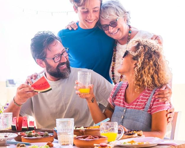 Famiglia di più generazioni che mangia cibo vegetariano insieme sul campo della terrazza bella gente