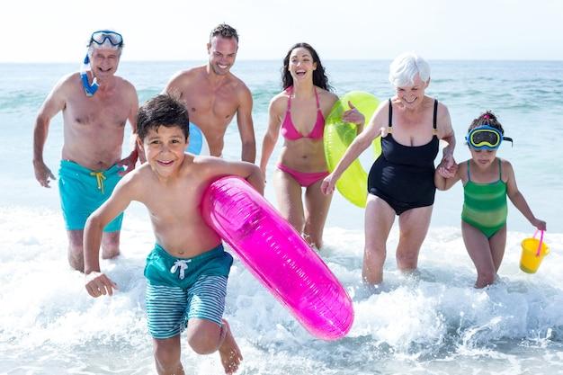 Famiglia di più generazioni che corre in spiaggia