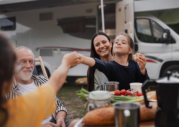 Famiglia di diverse generazioni che si siede e mangia all'aperto in auto, viaggio di vacanza in roulotte.