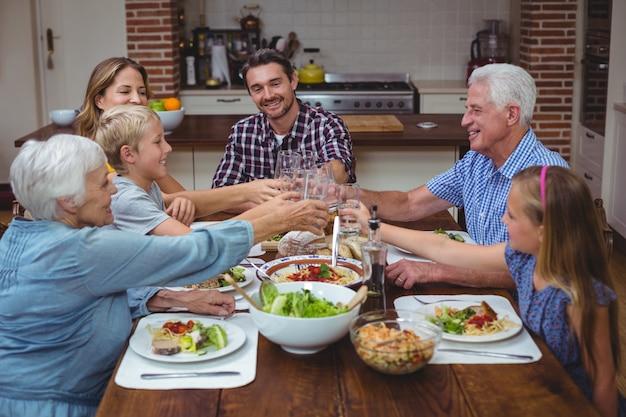 Famiglia di diverse generazioni che tosta drink mentre celebra il ringraziamento
