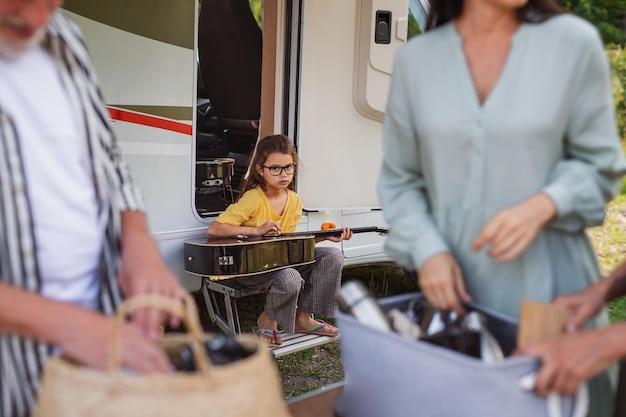 Una famiglia di diverse generazioni che disimballa in auto, viaggio di vacanza in roulotte.