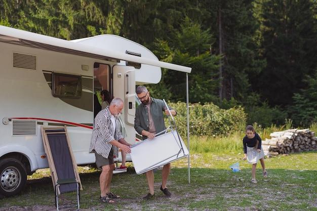 Famiglia di diverse generazioni che disimballa e parla in auto, viaggio di vacanza in roulotte.