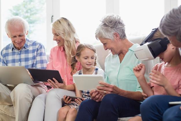Famiglia di diverse generazioni che utilizza tablet digitale, telefono cellulare e cuffie virtuali nel soggiorno