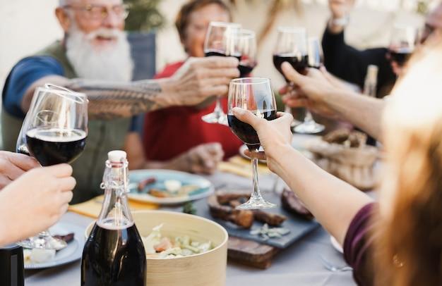 Persone multigenerazionali che esultano con il vino e mangiano all'aperto a casa