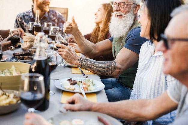 Persone multigenerazionali che si divertono a cenare nel patio con barbecue