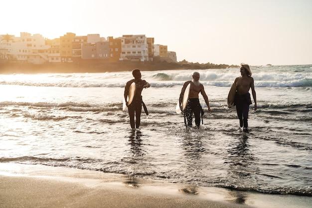 Amici surfisti multigenerazionali che si divertono dopo una sessione di surf sulla spiaggia