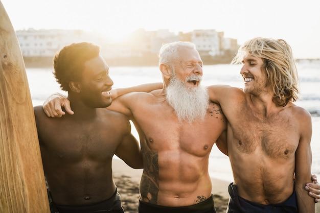 Amici surfisti multigenerazionali che si divertono sulla spiaggia dopo la sessione di surf - focus principale sul volto dell'uomo destro
