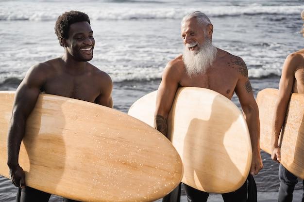 Uomini surfisti multi generazionali che si divertono sulla spiaggia - obiettivo principale sul viso senior