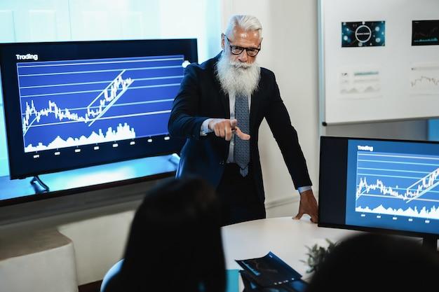 Team di trader multigenerazionale che tiene una conferenza sull'analisi del mercato azionario all'interno dell'ufficio degli hedge fund - focus sul volto dell'uomo anziano