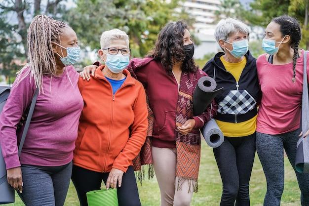 Donne multi generazionali che si divertono prima della lezione di yoga che indossano maschere di sicurezza durante l'epidemia di coronavirus al parco all'aperto - concetto di distanza sociale e sportiva - focus principale sul viso della ragazza centrale