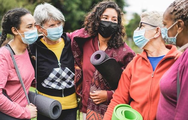 Donne multi generazionali che si divertono prima della lezione di yoga indossando maschere di sicurezza durante l'epidemia di coronavirus al parco all'aperto