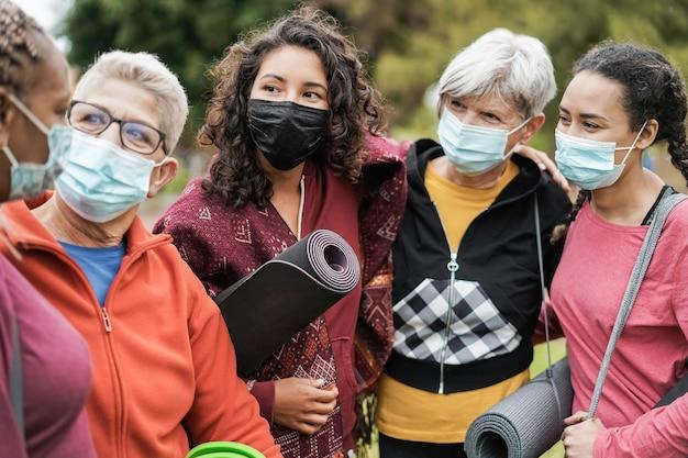 Donne multigenerazionali che si divertono prima della lezione di yoga indossando maschere di sicurezza al parco all'aperto