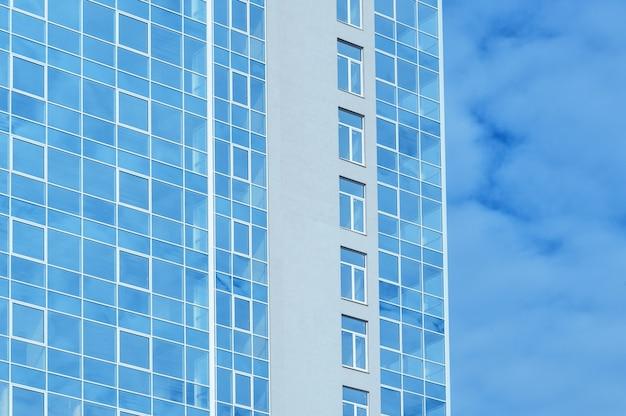 Edificio per uffici di vetro multipiano contro il cielo