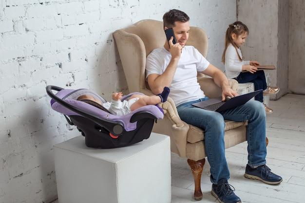 Concetto di multi-tasking, freelance e paternità - padre di lavoro con figlio neonato e figlia con computer portatile a casa ufficio