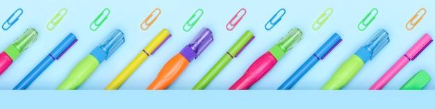 Articoli di cancelleria per ufficio e scuola luminosi multicolori in fila su uno sfondo blu con spazio di copia