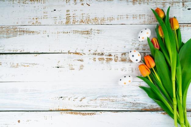 Pasqua multicolore dipinte di uova maculate sulla tavola di legno bianca con i tulipani