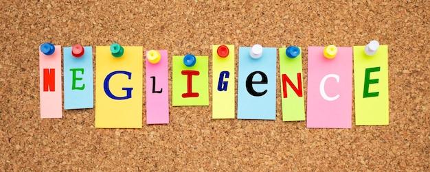 Note multicolori con lettere appuntate su una bacheca di sughero. parola negligenza.