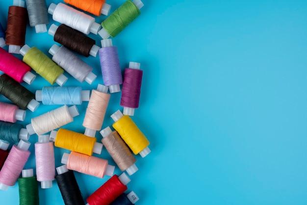 Fili per cucire multicolori su uno sfondo blu con uno spazio di copia per il testo, concetto di fili per cucire