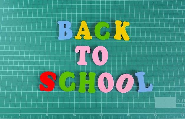 Testo multicolore torna a scuola sul tappetino da taglio verde.