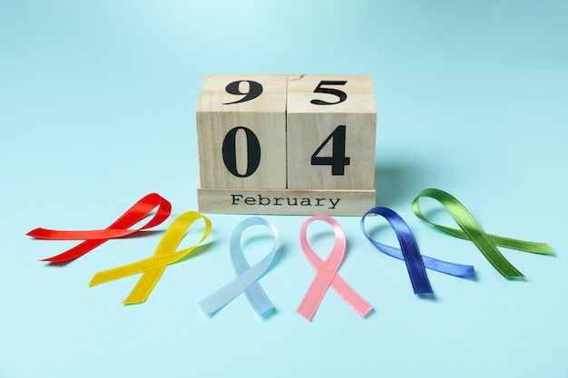 Nastri multicolori di consapevolezza e calendario con il 4 febbraio su priorità bassa blu