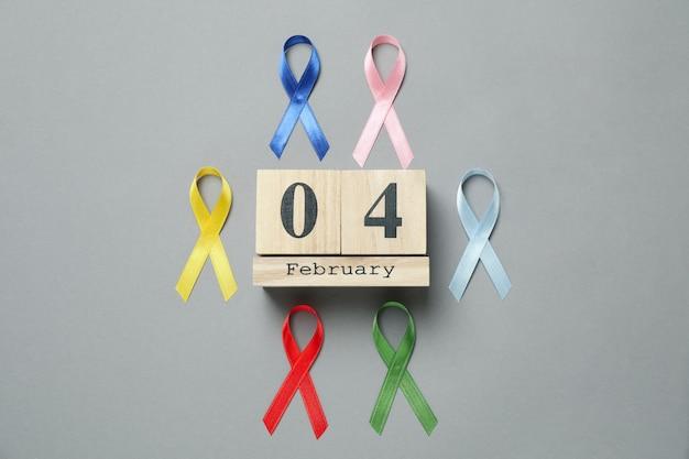 Nastri multicolori di consapevolezza e calendario con il 4 febbraio su gray