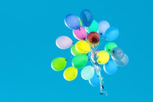 Palloncini multicolori che volano nel cielo blu. evento festivo