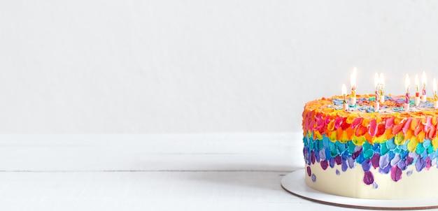 Torta di compleanno multicolore decorata con candele accese. concetto di auguri di buon compleanno.