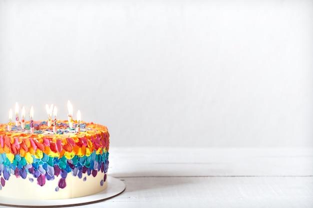 Una torta di compleanno multicolore decorata con candele accese. concetto di auguri di buon compleanno.