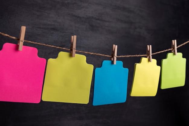 Le carte di carta bianche multicolori appendono con la molletta sulla corda. copia spazio. posto per il tuo testo.