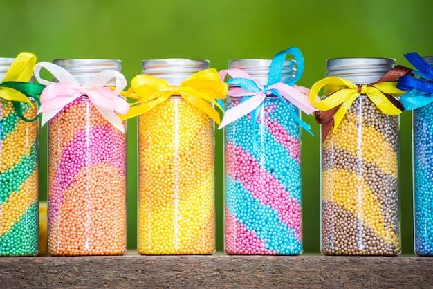 Bottiglie multicolori con schiuma per un bagno con archi su uno sfondo verde