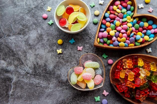 Caramelle multicolori, confetti e gelatina su una superficie nera