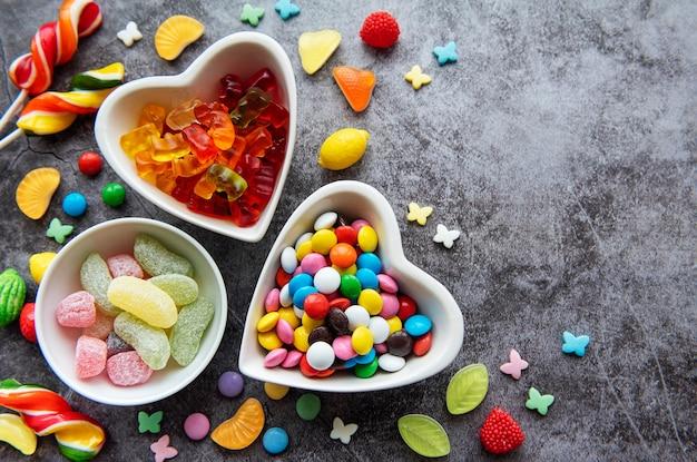 Caramelle multicolori, confetti e lecca-lecca su una superficie nera