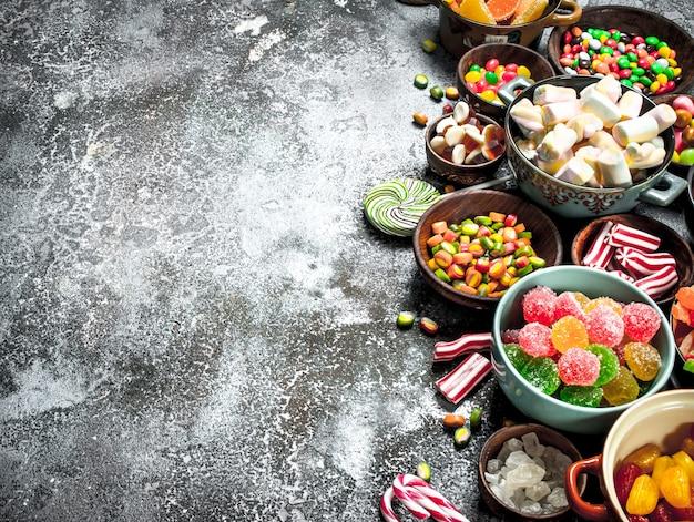 Caramelle multicolori, gelatina e marshmallow in una ciotola. su fondo rustico.