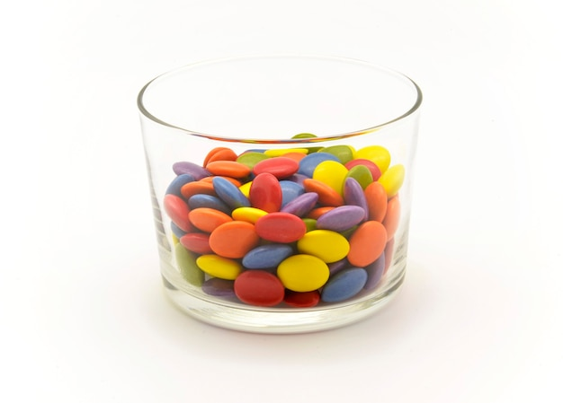 Caramelle di cioccolato multicolori in ciotola di vetro