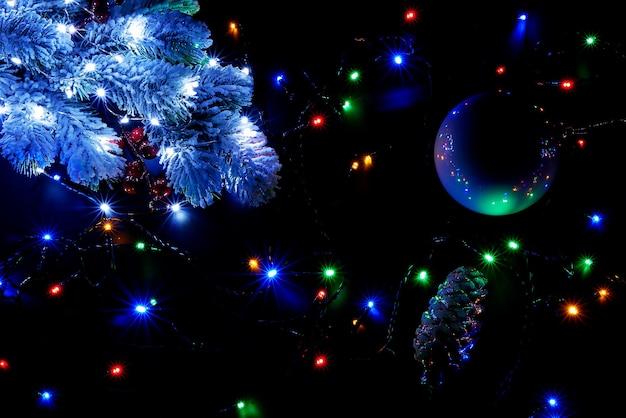 Luci di natale multicolori e albero di neve sono illuminati su sfondo nero, vista dall'alto.